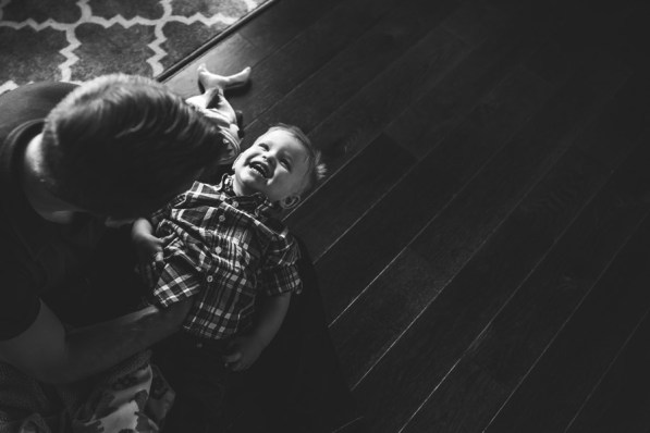 A young boy laughing while being tickled by his dad during a Redmond WA family photography session.