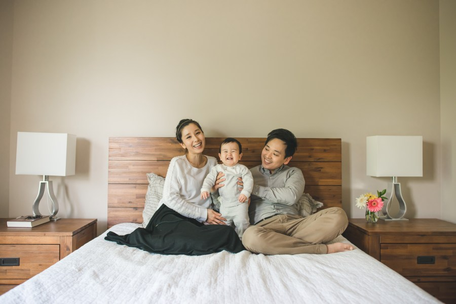 Family of three sitting together on a bed smiling at Issaquah family photographer