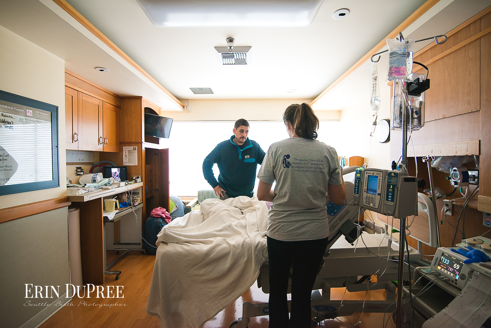 Man and woman standing around a hospital bed Seattle Birth Photographer