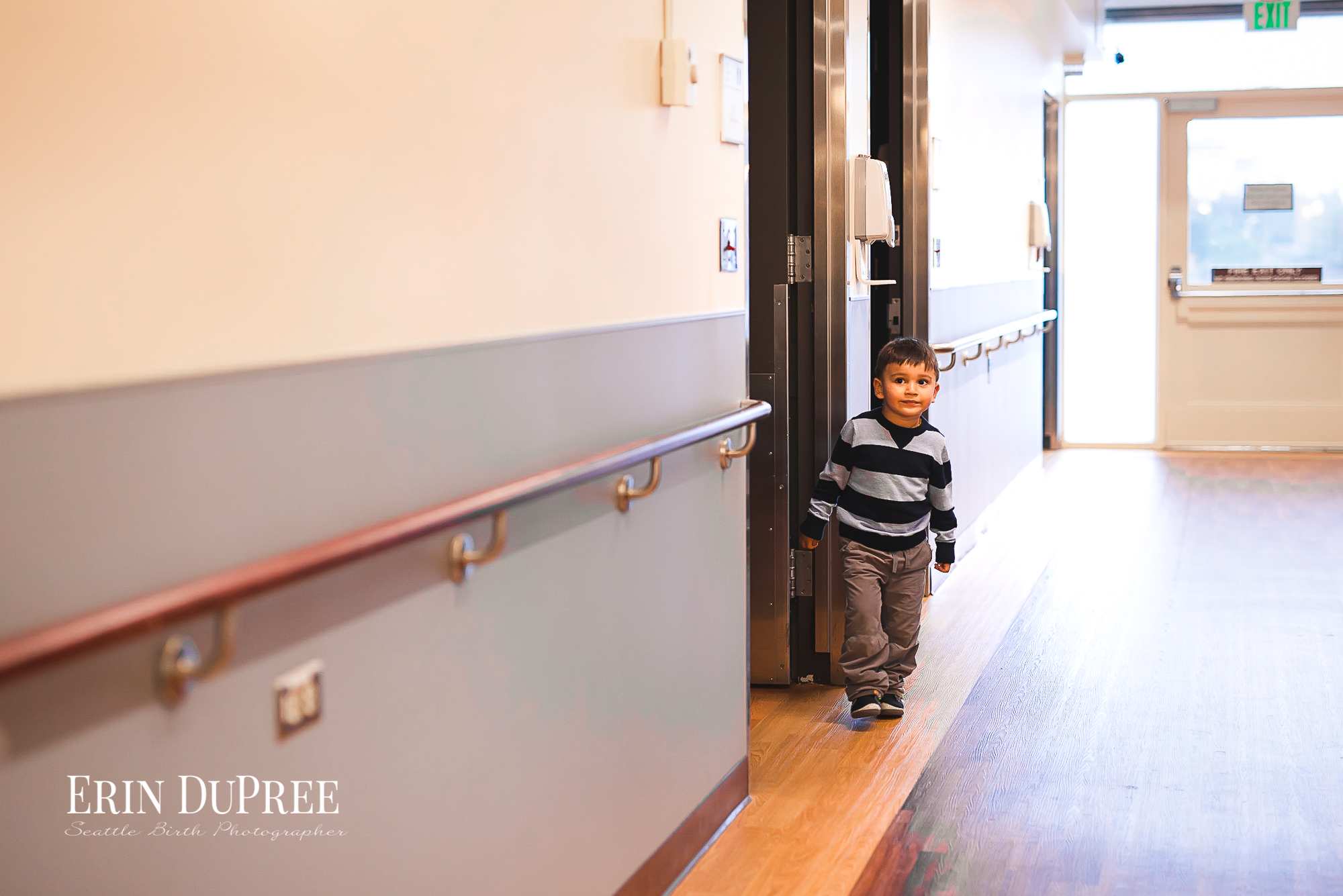 Young boy in hallway of Childbirth center in Seattle wa by Seattle Birth Photographer