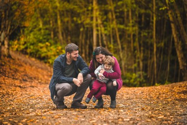 Parents and small boy smiling with fall leaves around by Bellevue Family Photographer