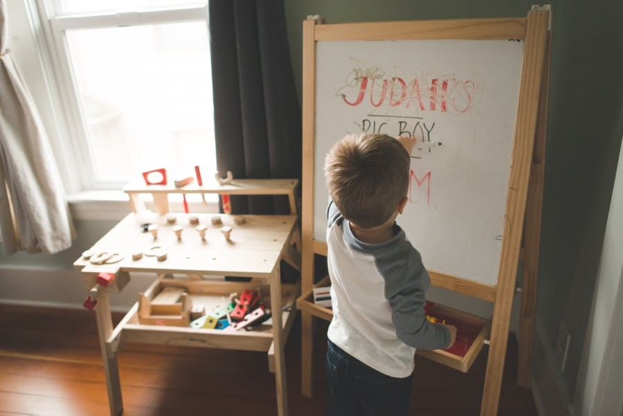 Young boy writing on a whiteboard in his playroom Seattle Newborn Photographer