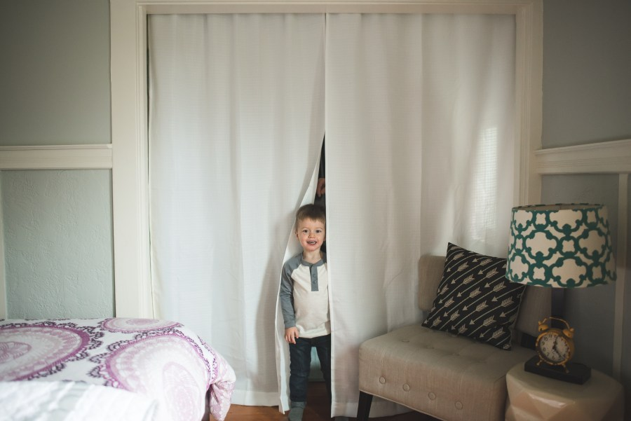 Toddler boy standing between white curtains by Seattle Newborn Photographer