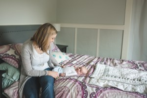 Mother and newborn baby on a bed by Seattle Newborn Photographer