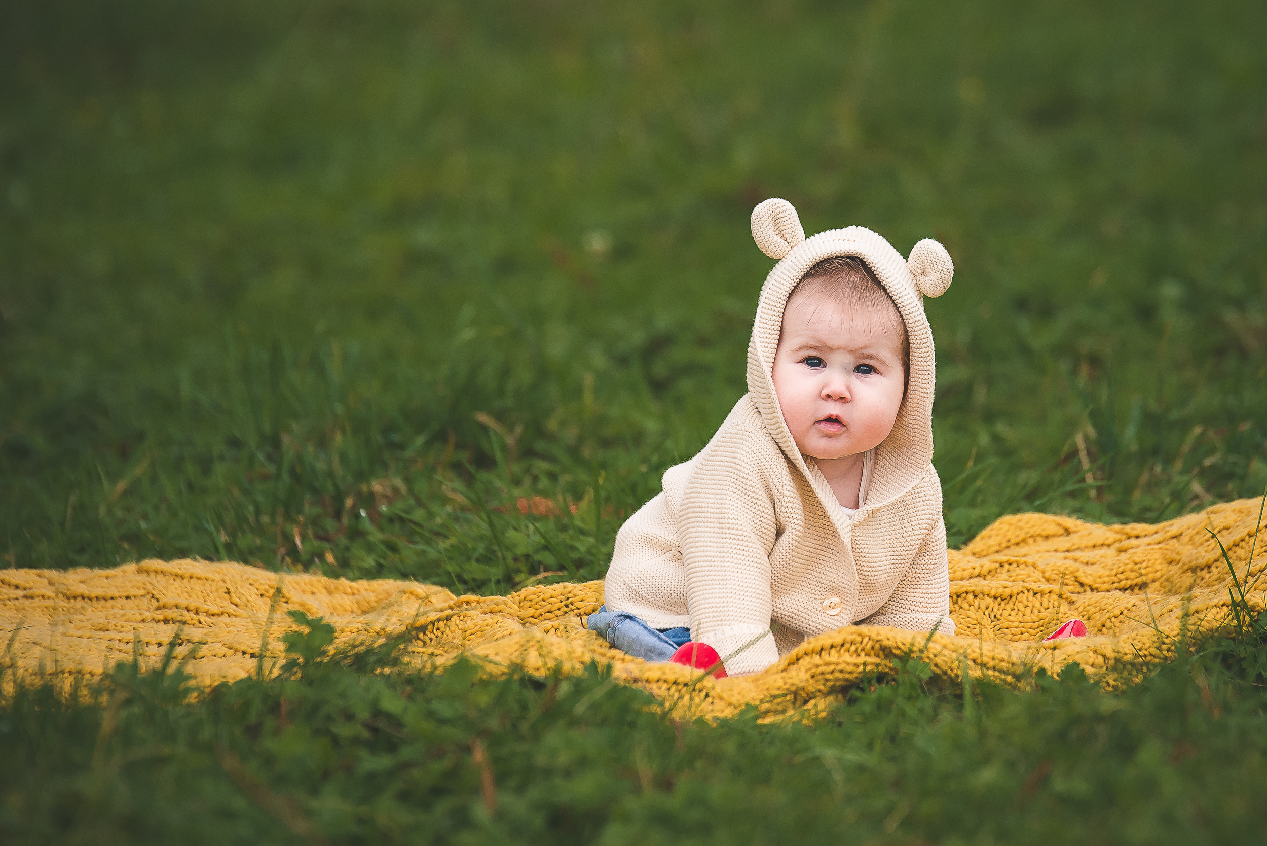 Seattle family photographer photo of Baby sitting on yellow blanket in the grass