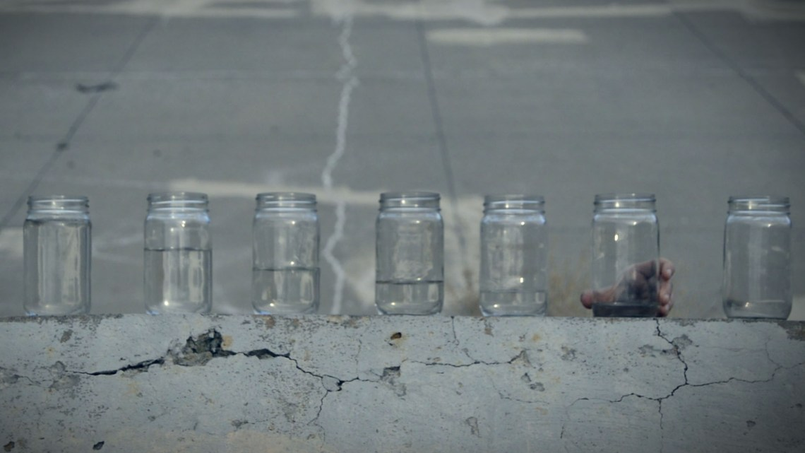 jars of water with hand to make sound, video still