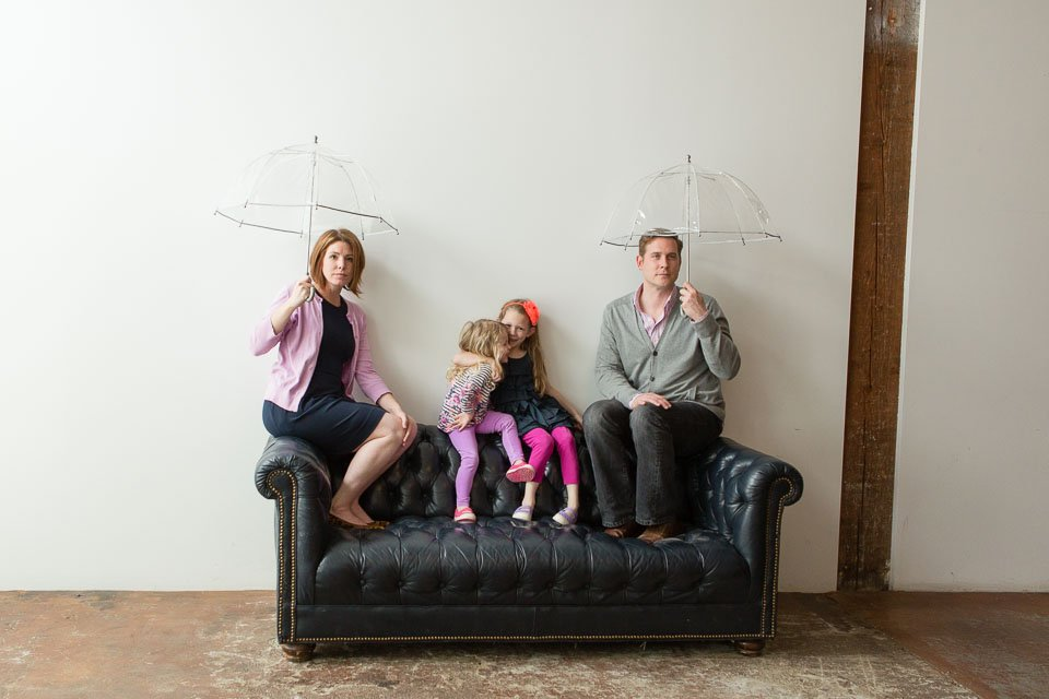 Family of 4 with umbrellas on couch
