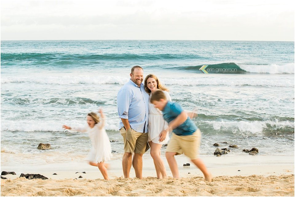 Family on beach with kids running blurred around their parents Kauai
