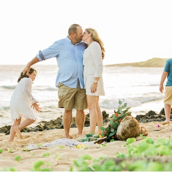 parents kissing two children playing Kauai beach Shipwrecks