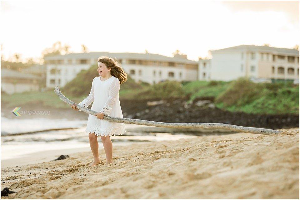 little girl white dress dragging stick Kauai beach windblown hair