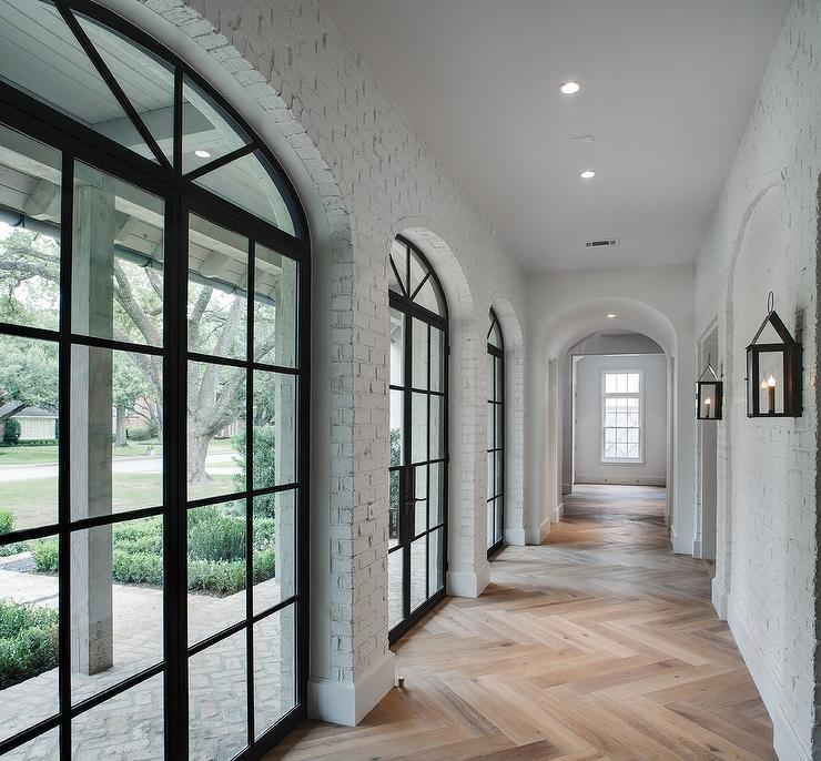 white-brick-hallway-arched-windows-carriage-wall-lanterns.jpg