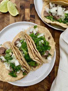 carne asada tacos with lime wedges