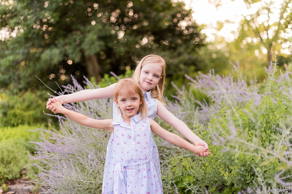 Sisters posing together for Authenitic Family Portraits at Greenspring Garden in Alexandria, VA by Alexandria Family Photographer, Erin Tetterton