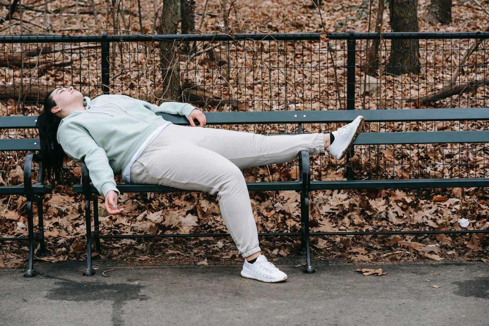 tired woman lying on bench in park