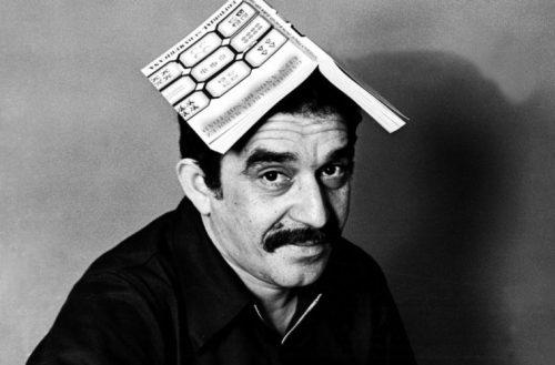 Gabriel García Márquez posando con un libro suyo