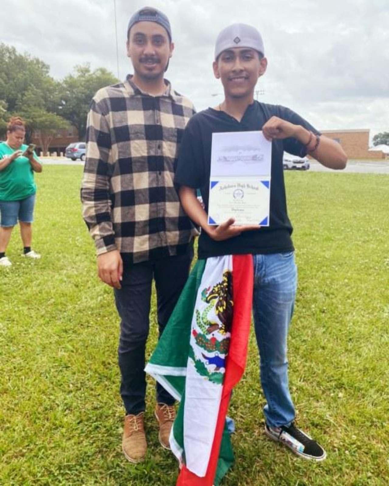 Entregan diploma chico bandera graduacion