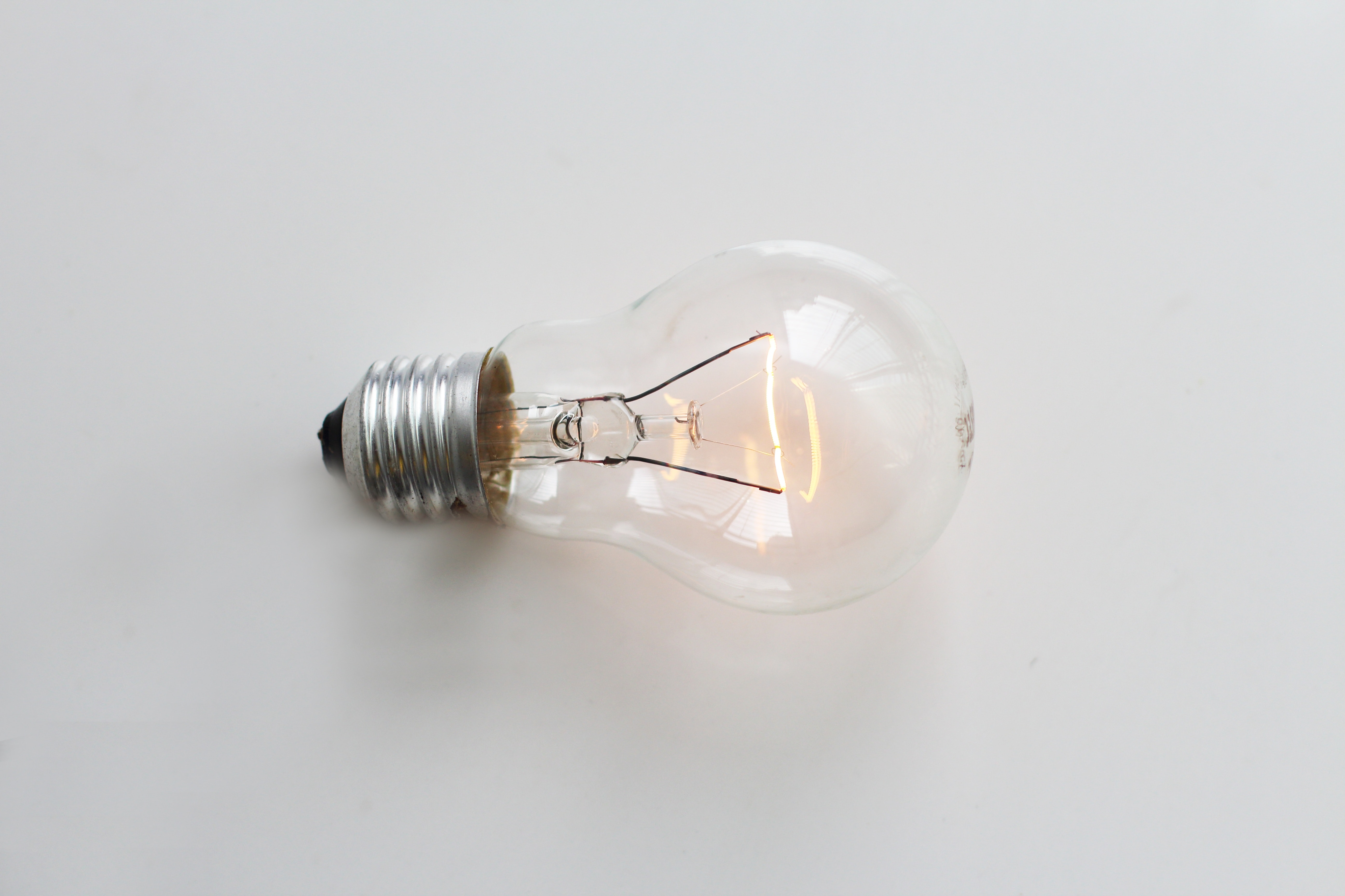 clear light bulb sitting on a white table