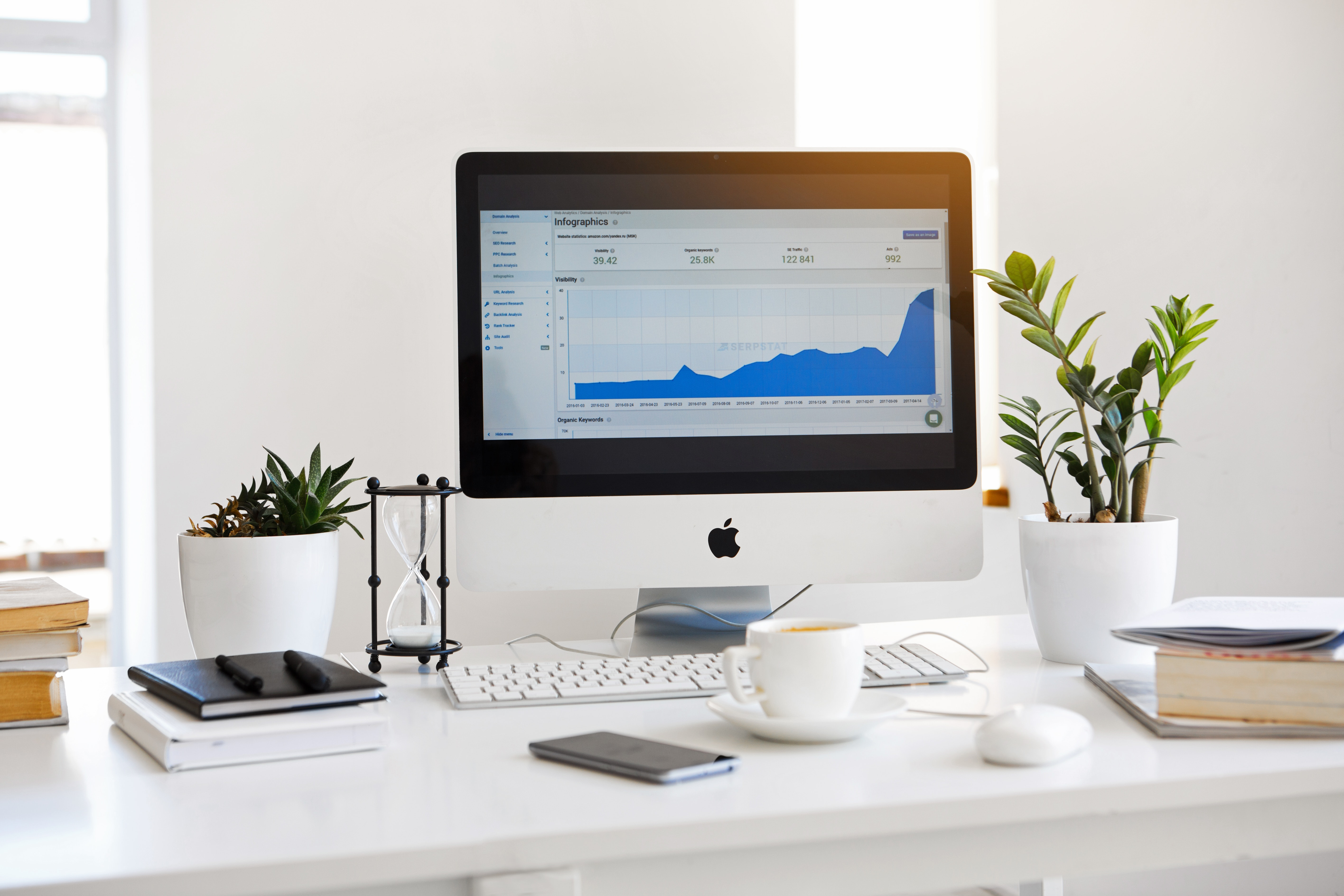 desktop computer displaying google analytics on a white table next to a plant
