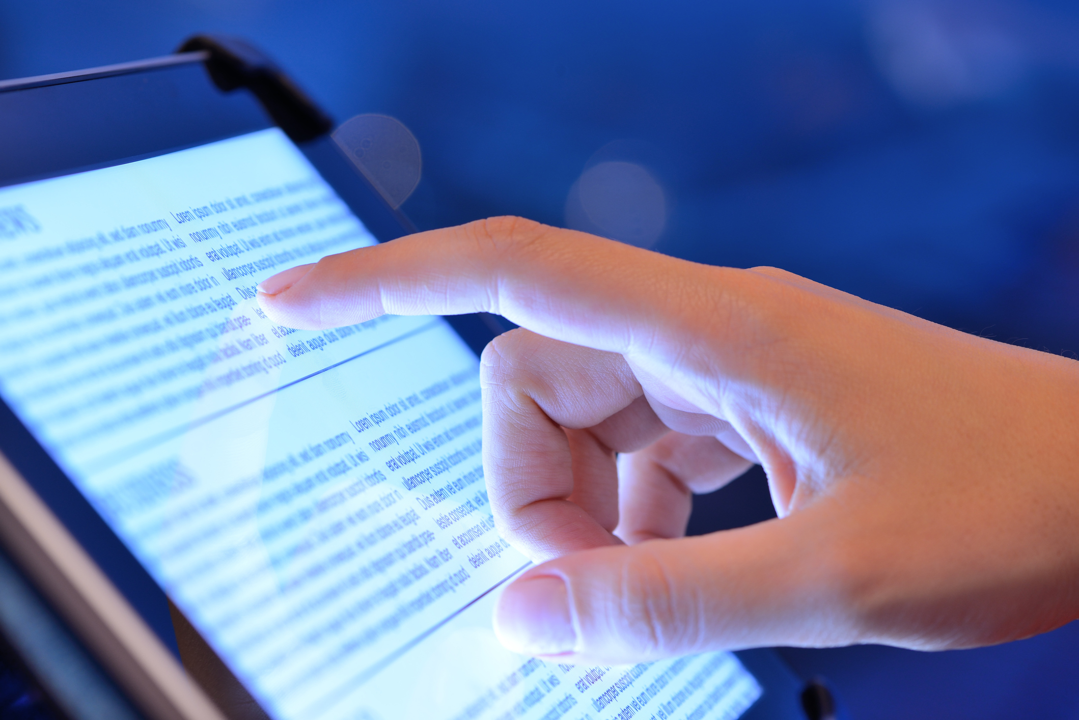 Person touching tablet with finger to scroll and read