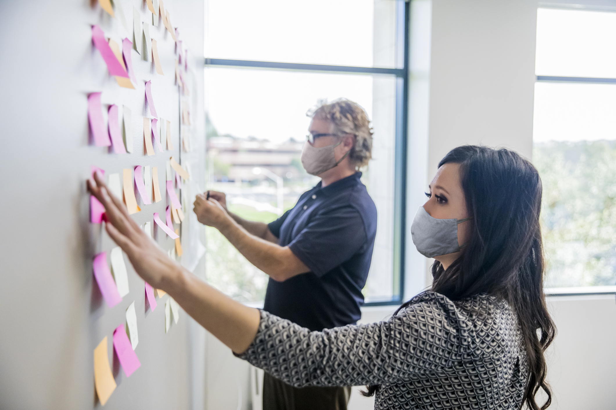 man and woman putting post-it notes up on wall wearing masks