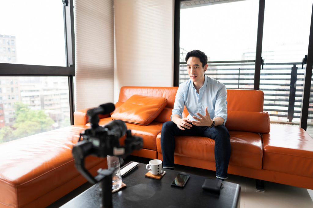 Man sitting on leather couch talking to camera