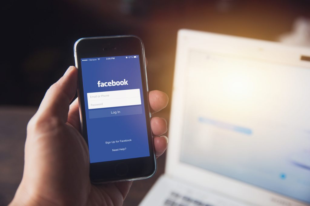 person holding cell ohone with facebook login on screen
