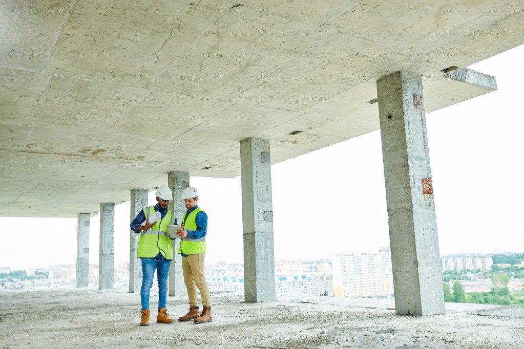 Two men in protective helmets and waistcoats discussing construction plan while standing under ceiling of unfinished building