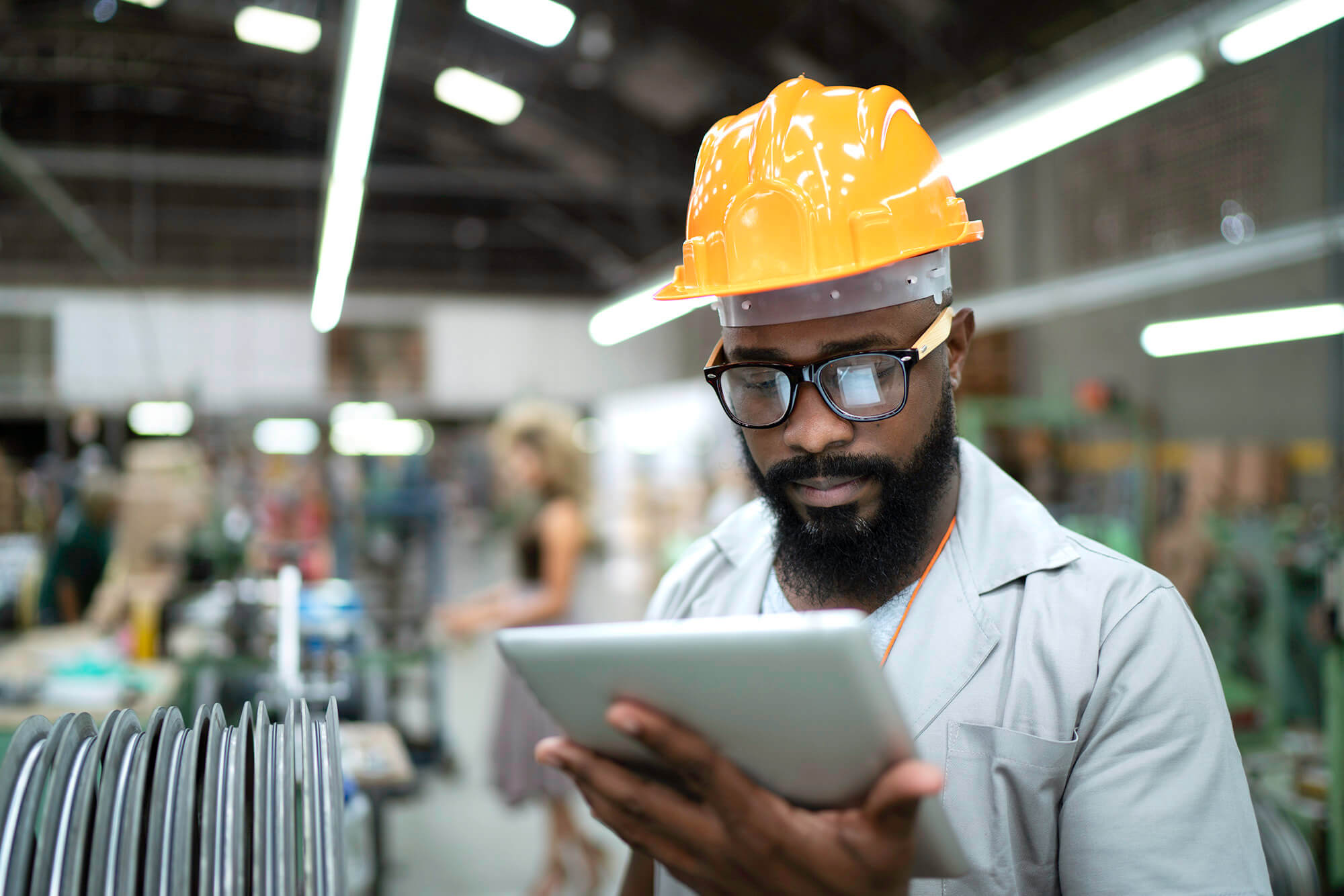 Building material worker is scrolling through tablet inside of warehouse