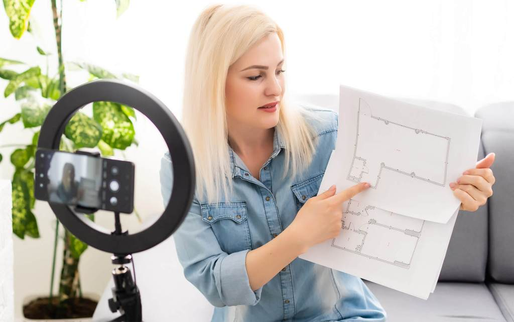 female architect hold blueprint up to ring light with phone recording in center