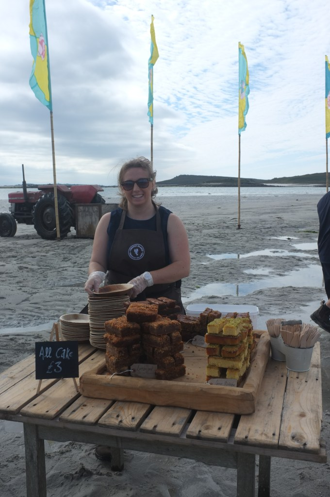 A woman sells cakes from a pop-up stall during the Low Tide Event in the Isles of Scilly