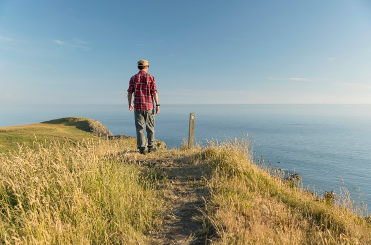 Man looks out to sea as he walks along the Southern Upland Way