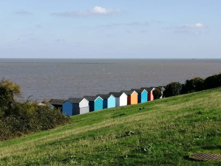 Colourful beach huts on grassy Tankerton Slopes overlooking Thames Estuary