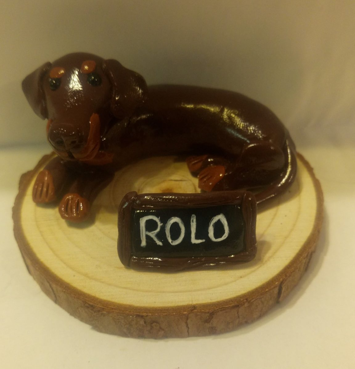 Clay dachshund lying on wooden plinth with name tag