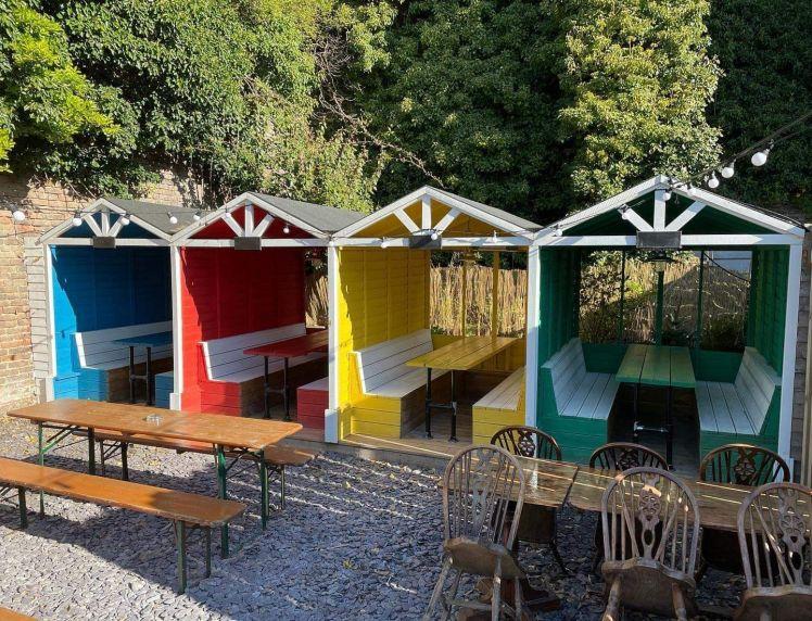 Colourful beach huts in the garden of the Marina Fountain, St Leonards