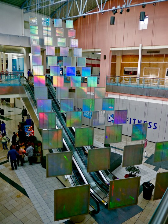 """52, 36"""" x 36"""" suspended, glowing, colorful rainbow prism panels hang suspended in this light art installation"""