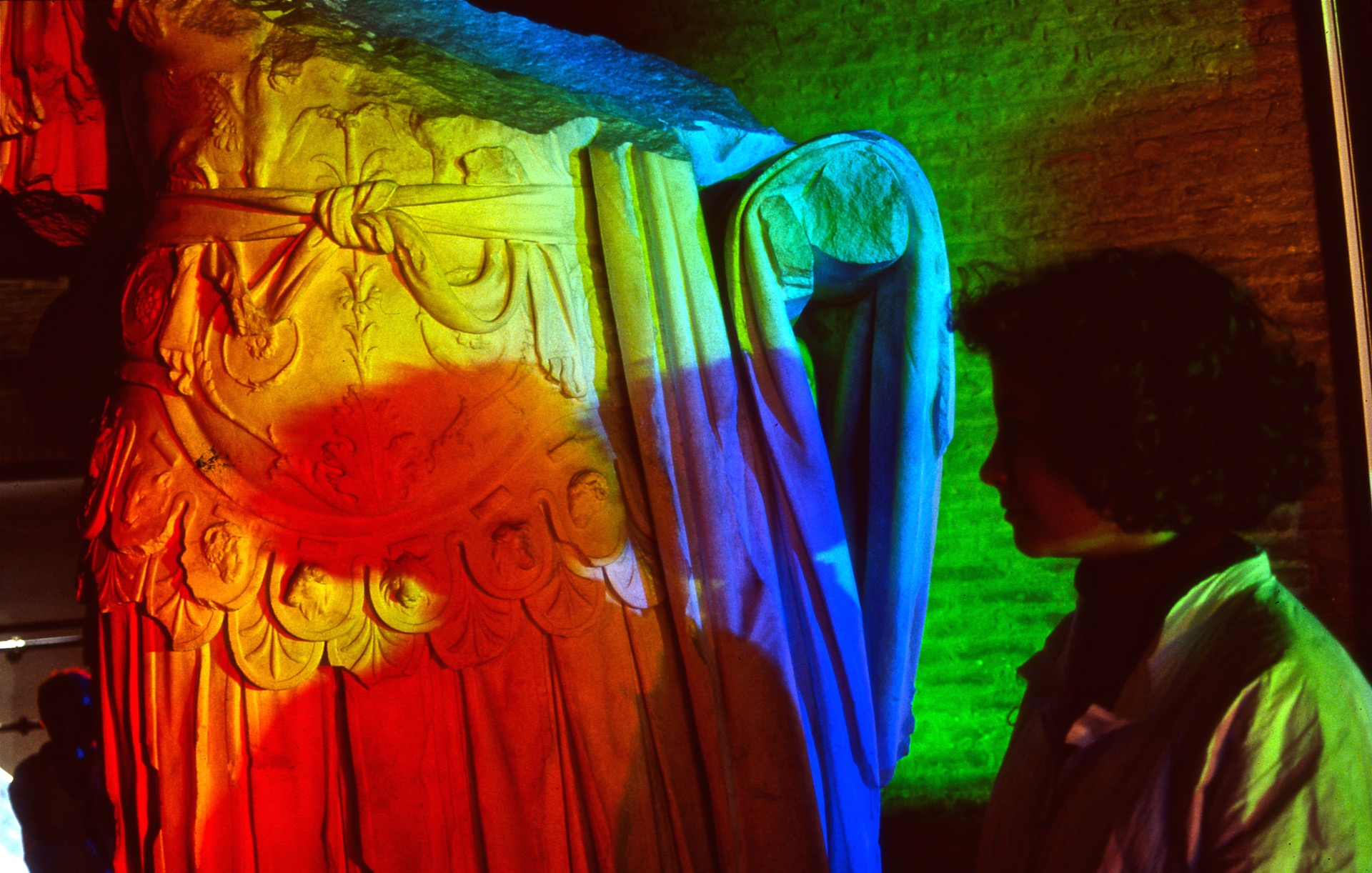 woman creates multiple colored solar spectrum shadows on an ancient Roman marble sculpture