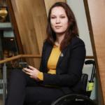 Zakelijk geklede jonge vrouw in rolstoel met telefoon in hand