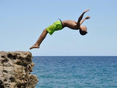 Op een fraaie manier een duik nemen vanaf de rotsen