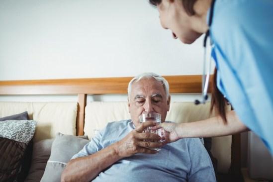 hombre mayor haciendo bebiendo en cama