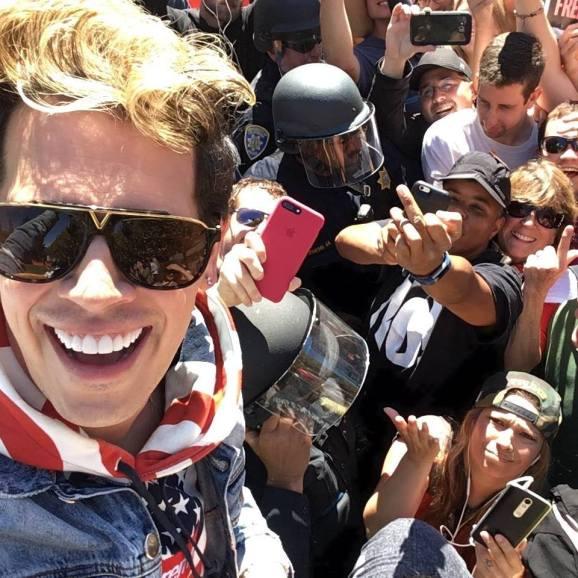 Milo Yiannopoulus sonríe frente a decenas de manifestantes en su contra dispersados por la policía. (Facebook)