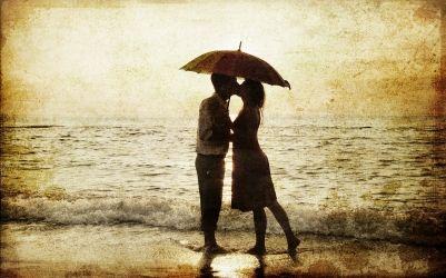 Pareja romántica besándose delante de una puesta de sol.