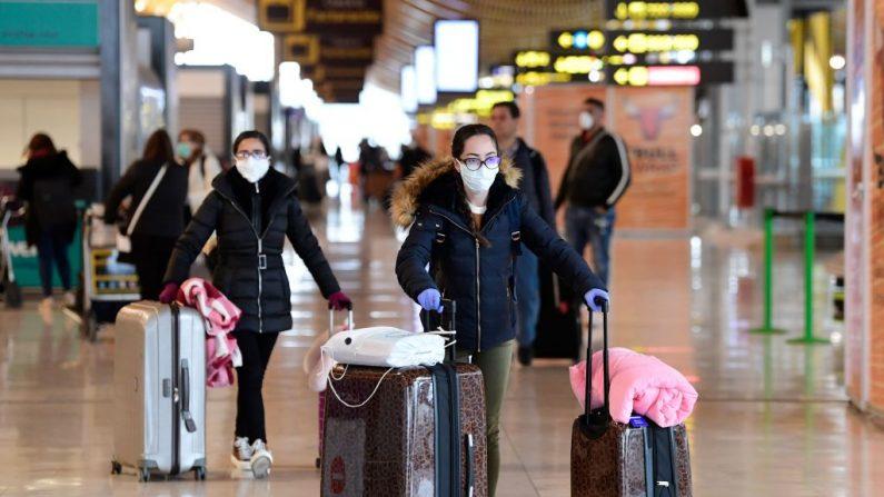 Los pasajeros que llevan mascarillas y guantes como medida preventiva para covid-19 empujan los carros en el aeropuerto Adolfo Suárez de Barajas, España, el 20 de Marzo del 2020. (JAVIER SORIANO/AFP vía Getty Images)