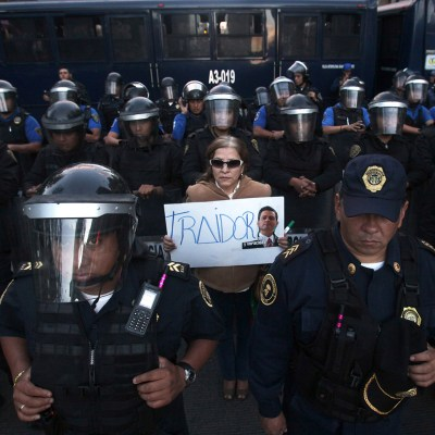 In this Dec. 21, 2013 photo, a woman holds a sign that reads in Spanish