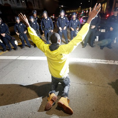 A protester pleads with police Wednesday, Nov. 9, 2016, in Oakland, Calif. Police in Oakland blocked thousands of people protesting Donald Trump's election from getting onto a highway Wednesday night. The crowd chanting and waving signs gathered in Frank Ogawa Plaza in downtown Oakland in the afternoon. (AP Photo/Marcio Jose Sanchez)