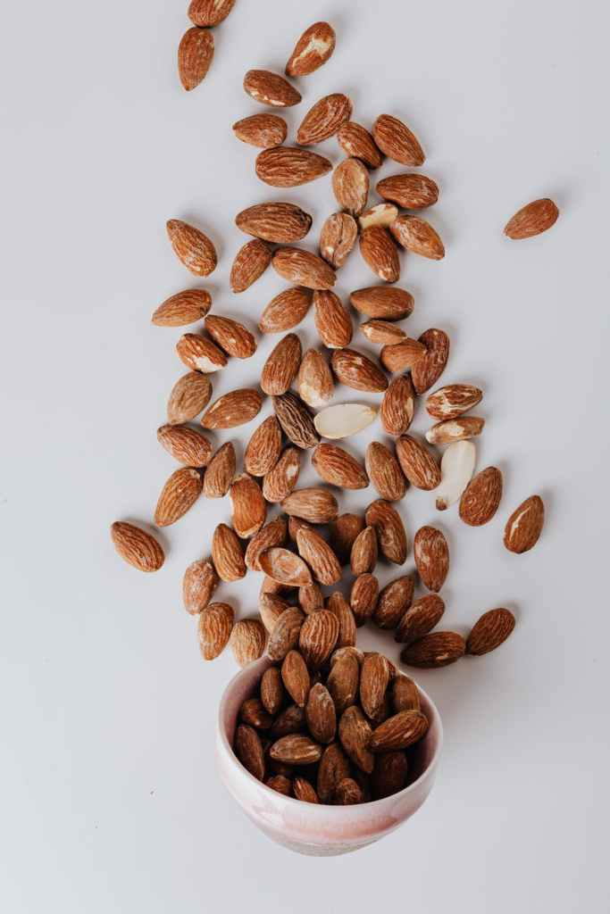 raw almonds spilled out of small ceramic bowl on table