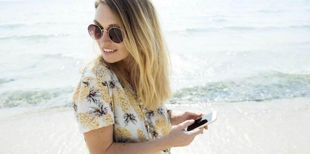 12-apps-de-viaje-mujere-fotografiando-paisaje-con-telefono-movil