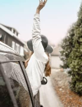 mujer saludando en auto de viaje