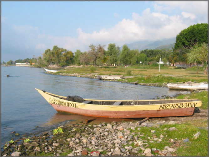 Typical fishing boat used by local fishermen pulled up on the shoreline of Lake Chapala.