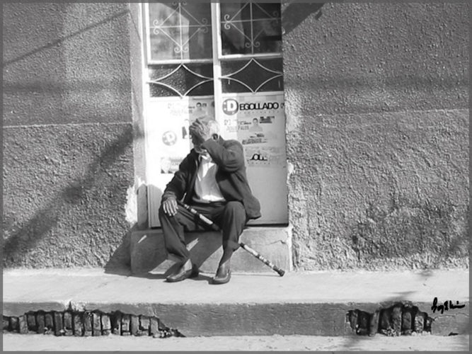 Man sitting in the door of his home in San Antonio, Mexico.