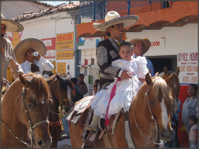 Little girl in a white dress rides on a horse with her dad.